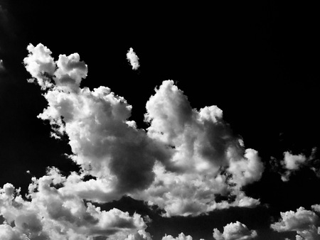 extracted: Isolated white clouds on black sky. Set of isolated clouds over black background. Design elements. White isolated clouds. Cutout extracted clouds.