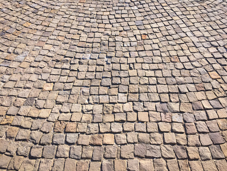 Stone pavement in perspective. Stone pavement texture. Granite cobblestoned pavement background. Abstract background of a cobblestone pavement close-up Archivio Fotografico