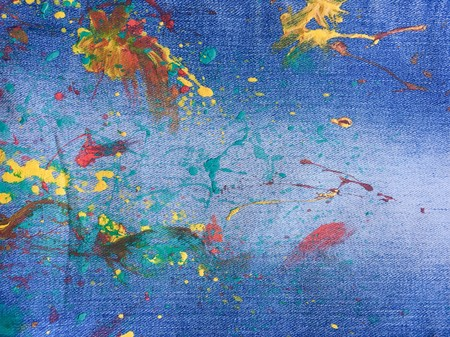 Texture of denim or colorful paint on blue jeans background. Drops of color paint on blue background of denim, jeans Stock Photo