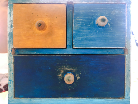 Colorful Wooden Drawer, vintage wooden commode at brick wall. Timber Cupboard Unit