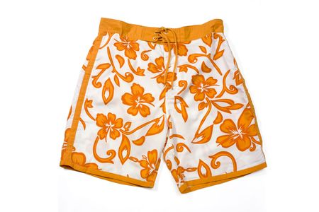 holidaying: Orange floral pattern swimming trunks isolated on white. Stock Photo