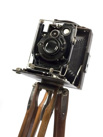 oldie: Old photographic camera with lens of bellows on wood tripod. Stock Photo