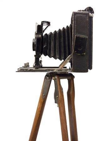 tripod: Old photographic camera with lens of bellows on wood tripod. Stock Photo