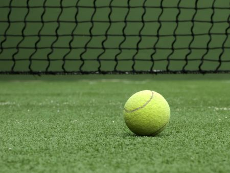 sportsman: Tennis ball on synthetic grass of paddle court.