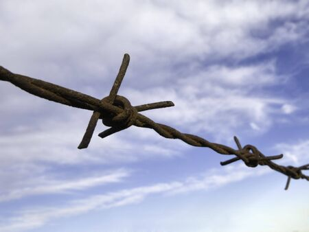 Rusty barbed wire fence on  sky background. Stock Photo - 3842254