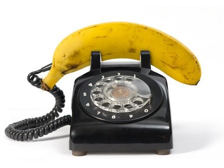 telefono antico: Banane fresche sul retro del telefono. Isolato su bianco.