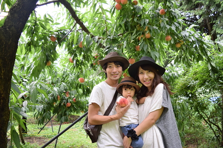 young family is smiling at flesh peach orchard Stock Photo