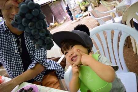 father and his son is eating grape Foto de archivo
