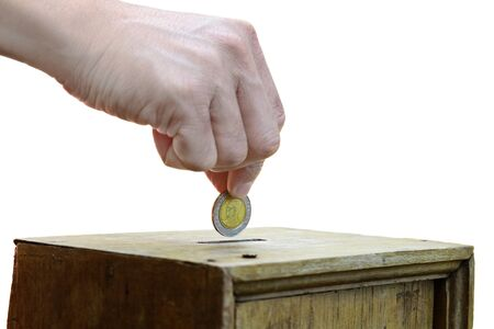 A man hand putting coin into a wooden box as donation isolated on white background