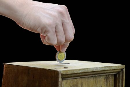 A man hand putting coin into a wooden box as donation isolated on black background Stock Photo