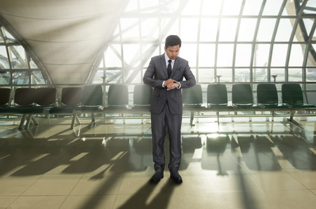 man in air: Business man looking at watch on his arm in the airport