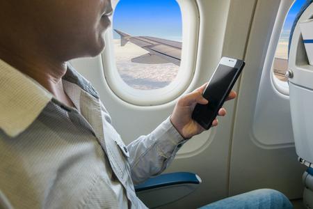 Man met behulp van slimme telefoon in het vliegtuig.
