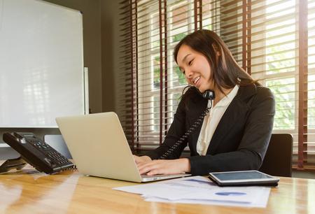 vrouw werkt in het kantoor en praten telefoon