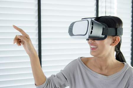 simulation: close up woman use virtual reality glasses ( VR ) in her office