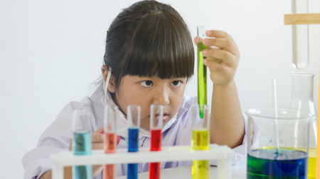 Asian children girl testing chemical in laboratory.