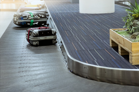 suit case on luggage conveyor belt at baggage claim in airport terminal. Imagens