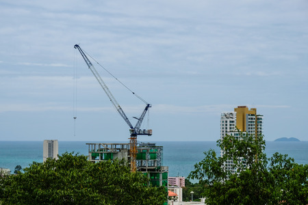 Crane build a building on the beach in front of sea