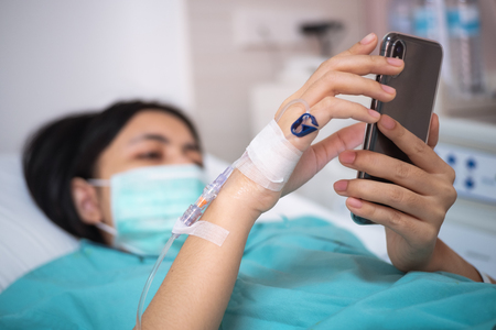 young woman patient lay on bed in hospital and use smartphone Stock Photo