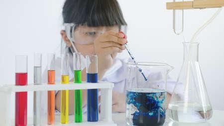 Asian children girl testing chemical in laboratory.