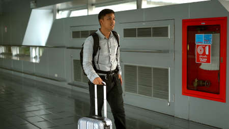 Young man with suitcase standing on the walkway airport