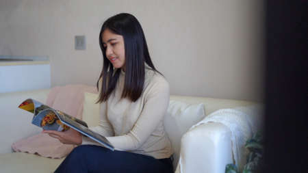 Young relax Asian woman reading magazine while sitting on sofa at home