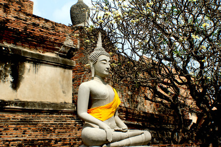 Buddha sitting peacefully in front of the temple wall. Stock Photo