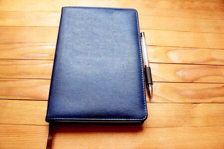 Note book and pen on wood background.
