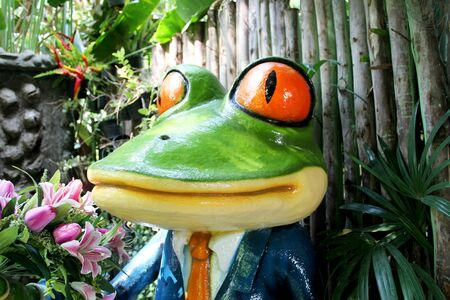 The green frog stands to welcome smiles in the cafe garden. Banco de Imagens