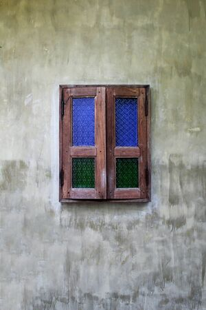 Green and blue glass of old wooden windows on old cement walls. Banco de Imagens