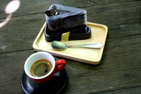 Espresso coffee in a red glass and chocolate in a wooden tray.And give you time to relax. Banco de Imagens