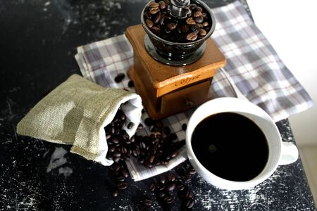 Coffee beans, grinders, coffee bags and black coffee in white cups. Banco de Imagens