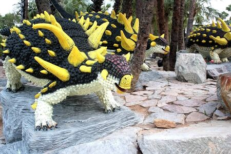 Dinosaur statue, black body and yellow thorns on the body