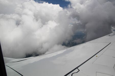 View of the clouds and airplane wing from the Inside photo