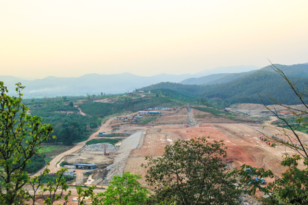 clay stone road in jungle: forest clearing for construction on sky background