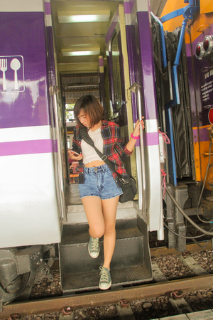 parting off: Young woman with a cell phone in her hand down from the train. Public transport. Stock Photo