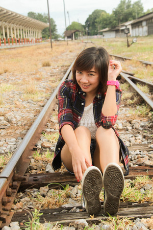 going nowhere: Beautiful girl sitting on rails Stock Photo
