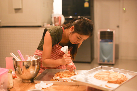 A young women is making homemade cake in the kitchen. Stock Photo