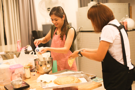 Two women are making homemade cake in the kitchen. Stock Photo