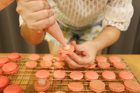 Squeeze the worms into the middle of macaron. woman enjoy to preparing macarons at home, top view, retro toned