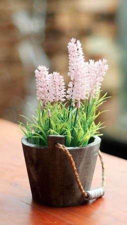 fresh flower vase on the table in the garden, soft focus, a little plant pot on the wooden table, vintage tone Imagens