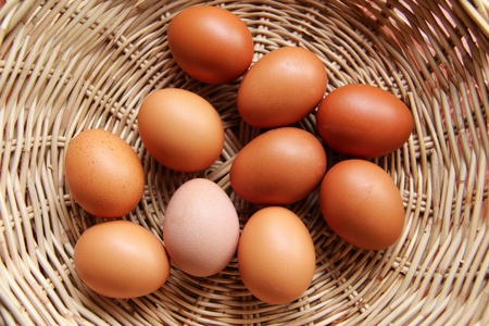 Raw eggs in wicker basket, top view Stock Photo