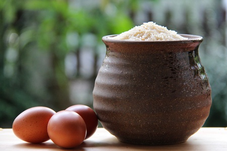 rice seed in jar and three eggs on wooden table in open kitchen with nature green background.