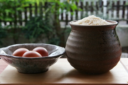 rice seed in jar and eggs in bowl on wooden table in open kitchen.