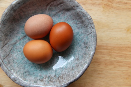 Three eggs in an ancient ceramic cup on wood table, top view