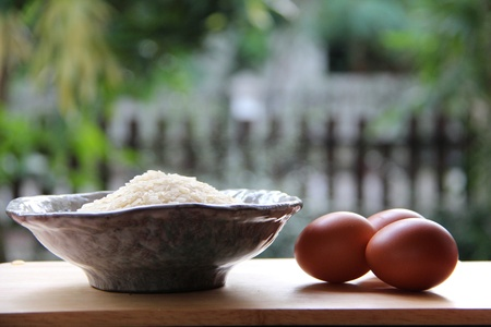 rice seed in bowl and eggs on wooden table in open kitchen.