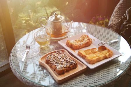 the afternoon hot tea with honey toast and whip cream on wood plate on table in the garden
