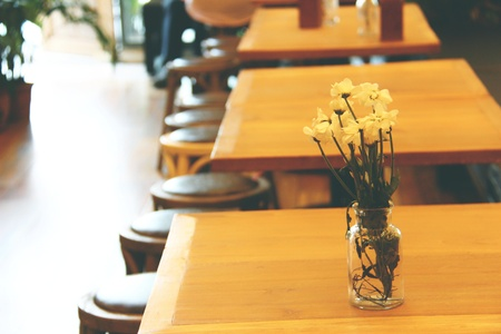 vase with lovely white flower on wood table, wood chairs and wood table in cafe, modern style