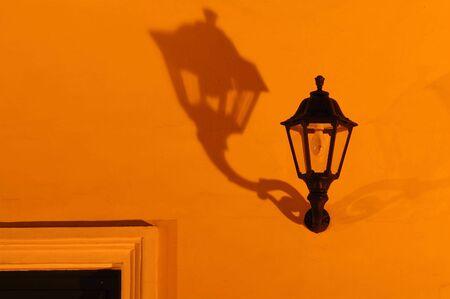 shadowed: An old street lamp shadowed on orange wall Stock Photo