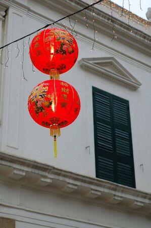 casa colonial: Dos linternas chinas que cuelgan delante de ventana colonial de la casa Foto de archivo