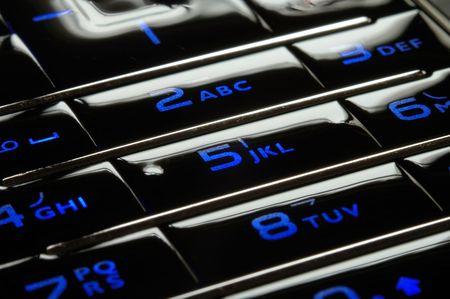 Close up shot of blue mobile keypad under dark environment photo